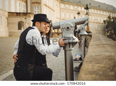 Loving young couple are looking into city view telescope in Prague - stock photo