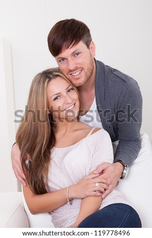 Loving young couple at home on the couch - stock photo