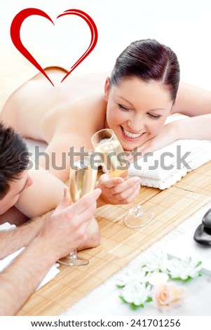 Loving young couple drinking champagne lying on a massage table against heart