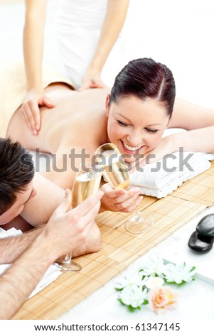 Loving young couple drinking champagne lying on a massage table in a spa center - stock photo