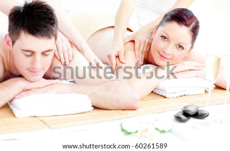 Loving young couple enjoying a back massage in a spa center - stock photo