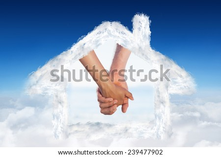 Loving young couple grasping hands against blue sky over clouds - stock photo