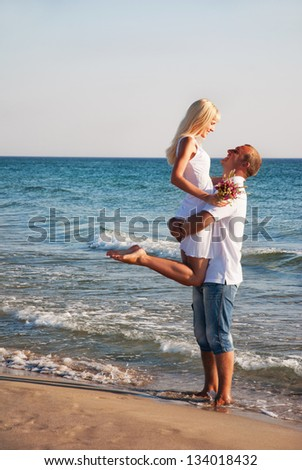 loving young couple hug on sea sand beach - stock photo