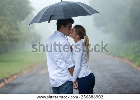 loving young couple in love under umbrella in the rain - stock photo