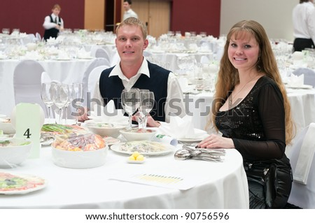 Loving young couple in restaurant at round white table. Dinner party - stock photo