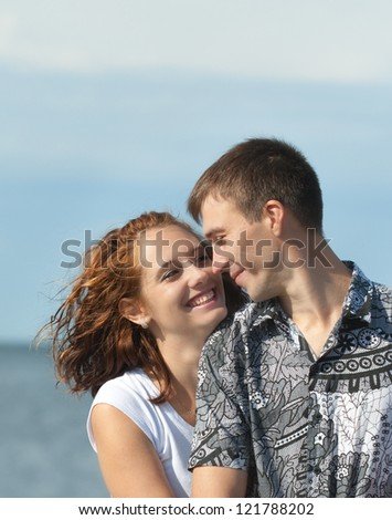 loving young couple is embracing at sea