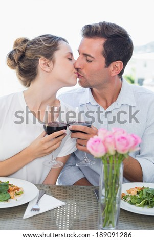 Loving young couple kissing as they hold wine glasses at food table