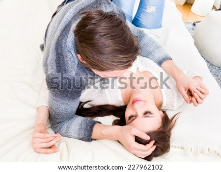 Loving young couple lying down on the bed, smiling and looking at each other. - stock photo