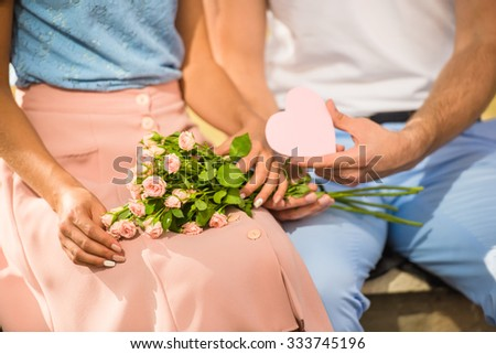 Loving young couple on a date with flowers and with a gift in the park - stock photo