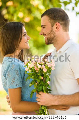Loving young couple on a date with flowers in the park