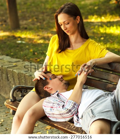 Loving young couple relaxing on the bench in park  - stock photo