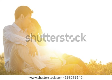 Loving young couple sitting on grass at park against clear sky - stock photo