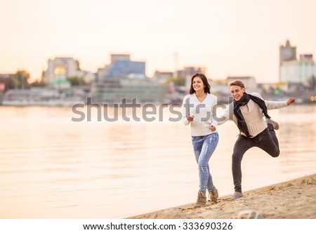 Loving young couple walk on the beach in autumn - stock photo