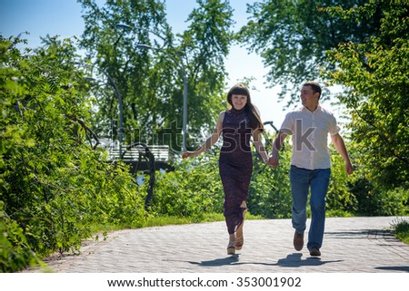 Loving young couple walk on the park at summer. Run together holding hands. Happy loving couple looking to each other. - stock photo