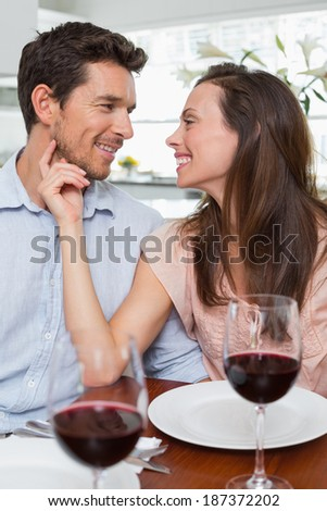 Loving young couple with wine glasses at dining table - stock photo