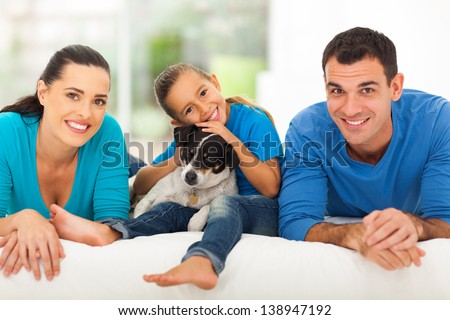 loving young family lying on bed at home with their pet dog - stock photo