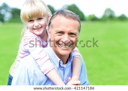 Loving young girl hugging her father from behind - stock photo