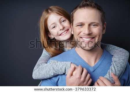 Loving young girl hugging her father from behind peeking over his shoulder at the camera with a playful smile, head and shoulders - stock photo