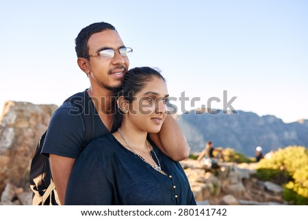 Loving young Indian couple standing together in nature gazing out at the view optimistically - stock photo