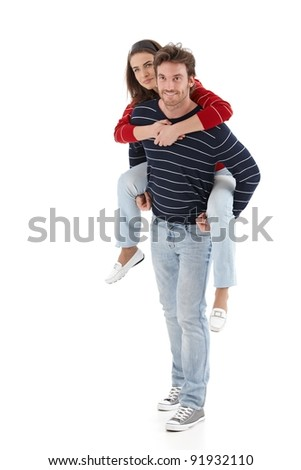 Loving young man carrying woman pickaback, smiling.? - stock photo