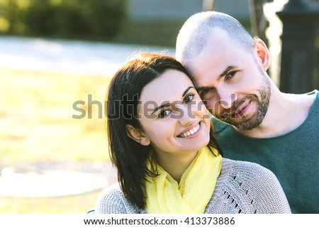 Loving young smiling couple boyfriend and girlfriend or husband with wife sitting on the bench in the park hug close up strong back light and lens flare cold toning - stock photo