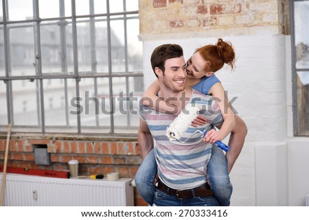 Loving young woman getting a piggy back ride from her handsome husband as she nuzzles him on the cheek while holding a paint roller indoors in the apartment - stock photo