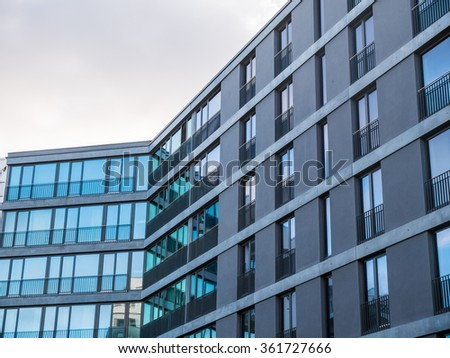 Low Angle Architectural Exterior of Modern Low Rise Residential Apartment Building with Large Windows and Gray Facade in Late or Early Lighting with Overcast Sky - stock photo