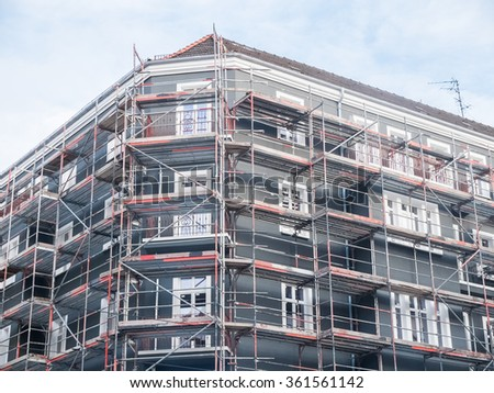 Low Angle Architectural Exterior View of New Residential Low Rise Apartment Building with Gray Facade Under Construction and Surrounded by Scaffolding