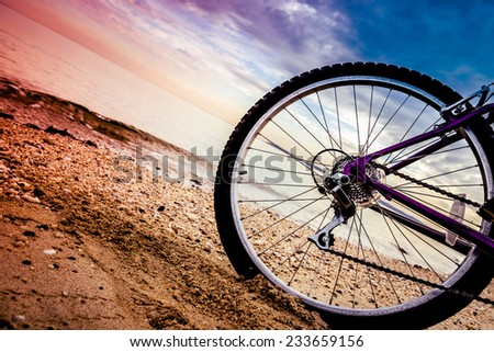 Low angle bike shot on the beach at sunset . Outdoors, nautical, biking, urban living, cross fitness and adventure background concept - stock photo