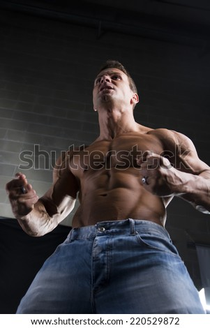 Low angle close up view of a strong young man with a muscular physique standing clenching his fists to emphasize his arm and shoulders muscles - stock photo