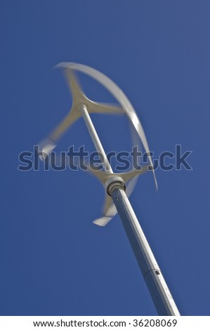 Low angle diagonal view of vertical axis wind turbine with motion blur on blades against a clear blue sky - stock photo