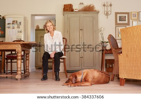 Low angle full length portrait of a senior woman smiling confidently while sitting in a wooden chair in her rustic style home, with her faithful pet dog lying on the floor near her feet - stock photo
