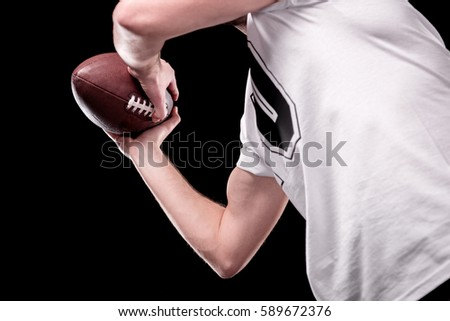 Low angle partial view of man in white t-shirt holding rugby ball isolated on black