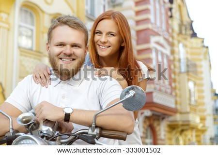 Low angle photo of a handsome bearded young man holding a handlebar and his beautiful red-haired girlfriend standing behind him smiling  - stock photo