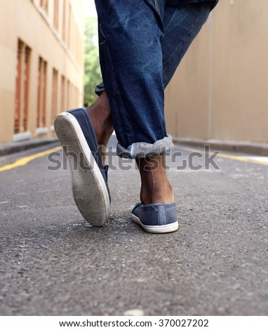 Low angle portrait of a man's legs and shoes from back - stock photo