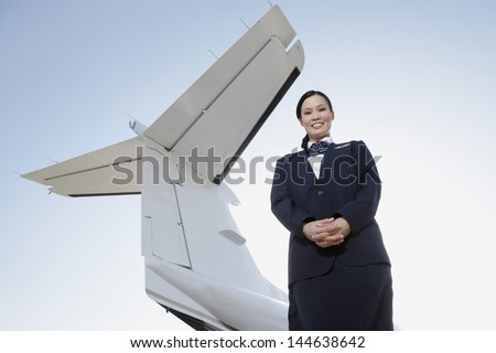 Low angle portrait of a smiling stewardess in uniform standing below wing of private aircraft against sky