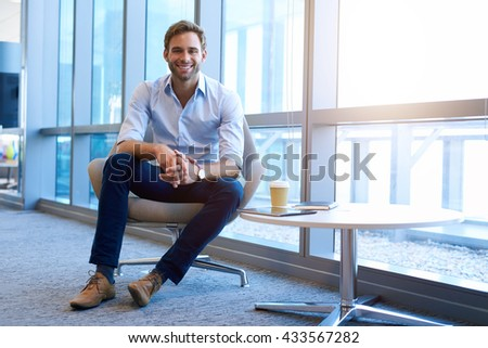 Low angle portrait of a young and handsome businessman, sitting in a modern chair in an open and bright corporate space, smiling at the camera with a warm and friendly expression - stock photo