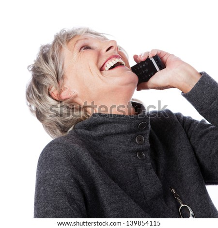 Low angle portrait of an attractive vivacious senior lady on the telephone laughing while enjoying the conversation, isolated on white