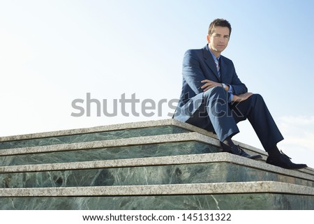 Low angle portrait of confident businessman sitting marble staircase against clear sky - stock photo