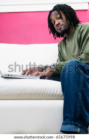 Low angle portrait of man with laptop - stock photo