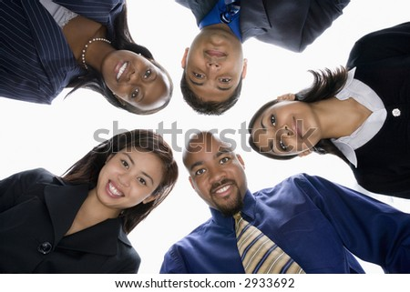 Low angle portrait  of multi-ethnic business group of men and women in huddle looking at viewer. - stock photo