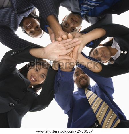 Low angle portrait  of multi-ethnic business group of men and women with hands in huddle. - stock photo