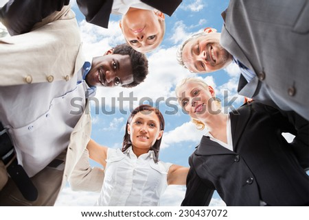 Low angle portrait of multiethnic business people forming huddle against sky - stock photo