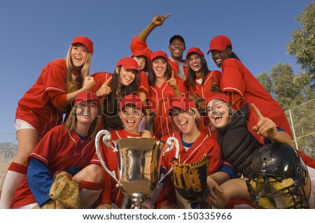 Low angle portrait of successful female softball team and coach with trophy celebrating against blue sky - stock photo