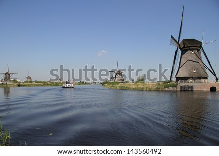 Low angle shot of Dutch windmills at a canal in Kinderdijk, The Netherlands - stock photo