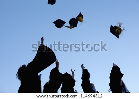 Low angle-shot of five graduates throwing their hats in the sky - stock photo