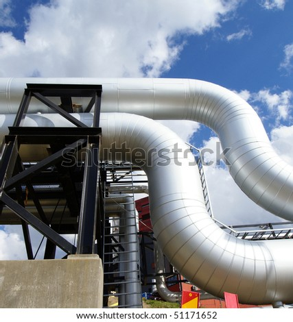 Low-angle shot of ladder and tanks refinery - stock photo