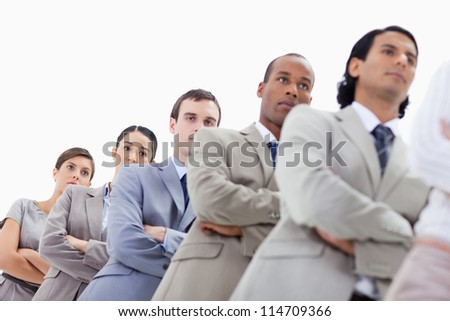 Low-angle shot of people dressed in suits crossing their arms in a single line with focus on the last two women - stock photo