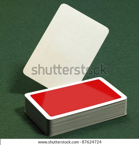 low angle studio photography showing a stack of red playing cards on green felt background - stock photo