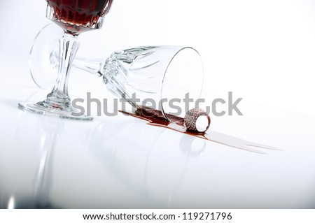 Low angle view across a reflective white countertop of a pool of spilled red wine from crystal wineglass lying on its side alongside a full cropped upright glass with copyspace - stock photo